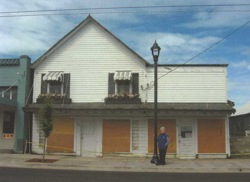 PHOTO FROM THE AUTHOR'S COLLECTION - The Noyer - Adams Building in 2017.    The two-story part was built in 1885.  The lean-to was added on in 1890.  Mrs. Tommi Tolstead stands near one of the new lamp posts installed during the 2017 road improvements.  The original windows were boarded up for protection against damage from the construction.