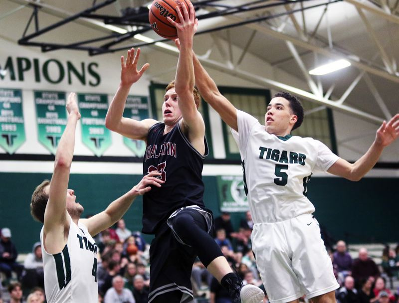 TIMES PHOTO: DAN BROOD - Tualatin High School senior Jack Rose tries to go up to the basket against Tigard senior Stevie Schlabach (left) and Drew Carter during Tuesdays game.