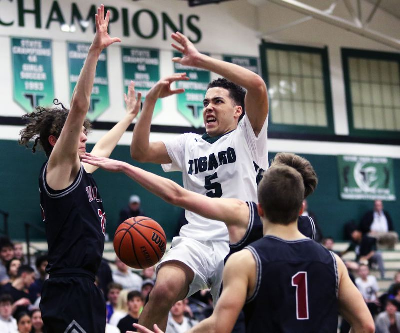 TIMES PHOTO: DAN BROOD - Tigard High School sophomore Drew Carter has the ball knocked away as he tried to get up to the basket during Tuesdays game.