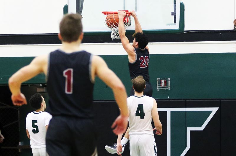 TIMES PHOTO: DAN BROOD - Tualatin High School junior John Miller finishes off a fast break with a two-handed dunk during Tuesday's game at Tigard.