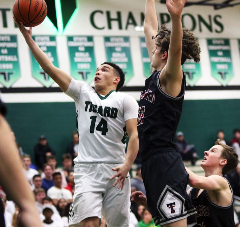 TIMES PHOTO: DAN BROOD - Tigard junior guard Max Lenzy goes up for layup during the Tigers' game with rival Tualatin on Tuesday.