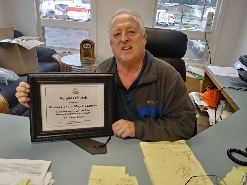 PMG PHOTO: JUSTIN MUCH - Woodburn Automotive proprietor Richard Edmonds holds a plaque he received from Peoples Church in Salem. Richard and his wife, Mary, donated a food-share van to the church.