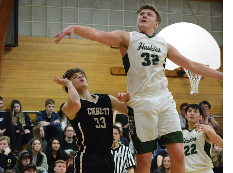 PAMPLIN MEDIA: DAVID BALL - North Marions Johnny Page soars through the air to block a shot by Corbetts Jake Newton during the third quarter of the Huskies 79-64 road win Tuesday.