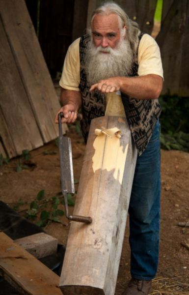 COURTESY PHOTO: DAVID ROGERS - David Rogers practices his craft of building with logs and restoring log structures with the same hand tools that were originally used to construct these historic buildings. He is shown here skinning the outer layers of this Alaska yellow cedar log with his drawknife.