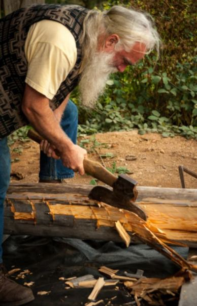COURTESY PHOTO: DAVID ROGERS - After four decades of building with logs, David Rogers, known as the log doctor, has launched his Cascadian School of Log Building and Design. Classes will begin this June in the Government Camp area. David is shown here using a broad axe to create a flat side to the logs rounded surface.