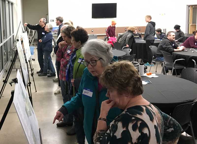 REVIEW PHOTO: SAM STITES - Community members review materials related to the multi-use trails and bike skills park proposed for Luscher Farm at last week's public forum, the latest in a series of opportunities to give input on the project.