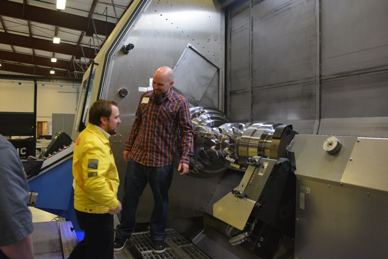 SPOTLIGHT PHOTO: COURTNEY VAUGHN - Mark Briel and Markus Mayr show visitors the WFL Millturn M80 machine at the Oregon Manufacturing Innovation Center R&D in Scappoose during a training demo Wednesday, Feb. 20. OMIC hosted manufacturing industry workers for a two-day training demo series.