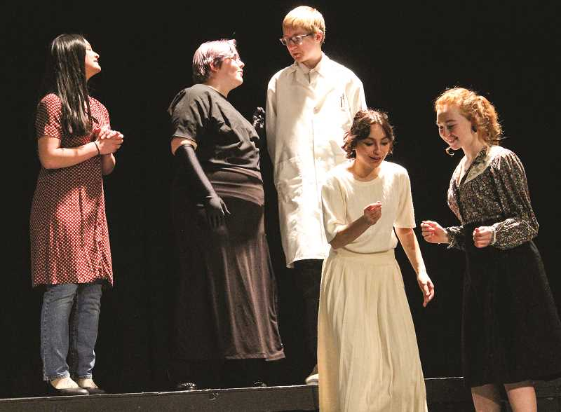 JASON CHANEY - Members of the Radium Girls cast rehearse a scene from the play on Tuesday afternoon. In the scene, main character Grace Fryer, played by senior Lynnette Taitano, admires a certificate she has received after sending funds to Madame Curie for her radium research. Pictured in the photo, left to right, are Sofia Gonzalez San Nicholas, portraying a society lady, Drew Finley as Madame Curie, Dallen Nixon playing the role of Dr. Von Sockocky, Taitano and Dakota Carpenter, who is cast as the Irene, the best friend of Grace Fryer.