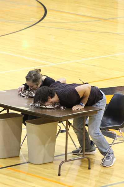 KRISTEN WOHLERS - Allison Byers (left) and Jeff Hillhouse devour cake at the closing assembly Friday, Feb. 22.