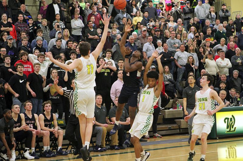 PMG PHOTO: MILES VANCE - Lake Oswego sophomore Wayne McKinney (center) launches a running one-handed shot from the right sideline to beat the clock and beat West Linn 60-59 at West Linn High School on Friday night.