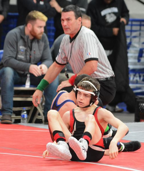 PMG PHOTO: DAVID BALL - Corbett sophomore Trey Conner rolls off his opponent after pinning No. 8-seed Gabe Chavez out of Hidden Valley in 19 seconds to open the 4A state tournament Friday.