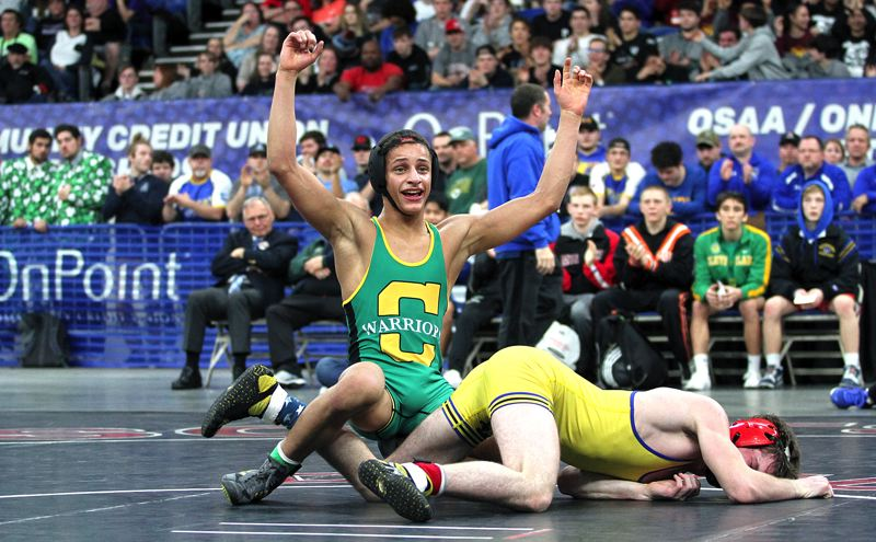 PMG PHOTO: MILES VANCE - Cleveland's Jontae Hardaway celebrates at the end of his 6-3 win overtime win against Newberg's Christopher Strange in the 120-pound championship match at the Class 6A state wrestling tournament at Memorial Coliseum on Saturday.