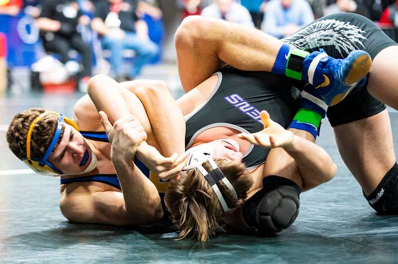 LON AUSTIN/CENTRAL OREGONIAN - Kyle Knudtson works to pin Ridgeview's Cole Jackson during the 182-pound finals. Knudtson went on to win the weight class championship, while Hunter Mode, 126, and Zach Mauras, 132 also won individual titles. The Cowboys finished second to Crescent Valley as a team.