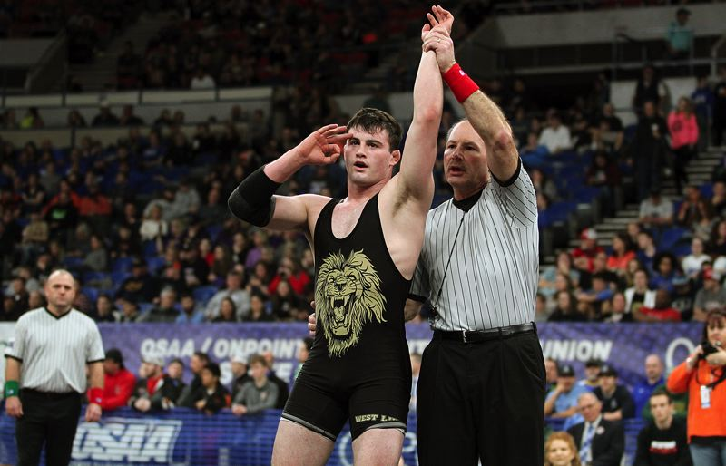 TIDINGS PHOTO: MILES VANCE - West Linn senior Sean Harman has his arm raised in triumph and signals three straight state titles with his other hand after winning the Class 6A state wrestling championship at 170 pounds on Saturday at Veterans Memorial Coliseum.