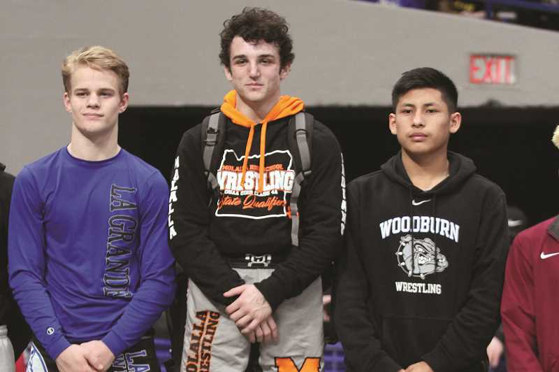 PHIL HAWKINS - Woodburn junior Freddy Hernandez (right) stands on the podium to receive his third-place medal in the 4A 126-pound wrestling bracket, along with champion Maximus Tate of Molalla (middle) and runner up Braden Carson of La Grande.