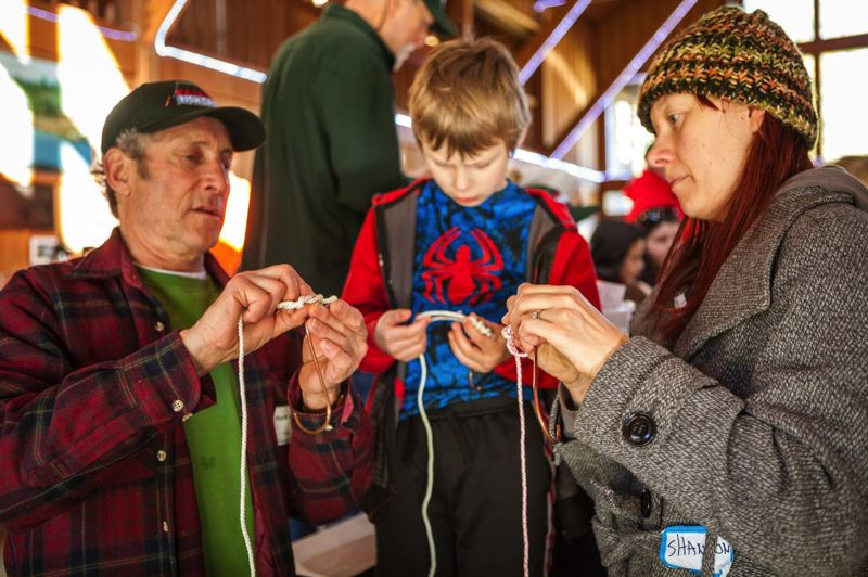 COURTESY PHOTO: NORTHWEST ASSOCIATION OF STEELHEADERS - Association of Northwest Steelheaders volunteer Huck Grimwood teaches Shannon Milliman and her son Phineas how to tie knots during last years fish camp.