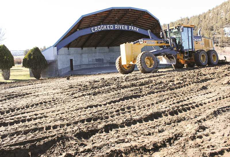 JASON CHANEY - City Street supervisor Scott Smith works on leveling the grassy hill in front of the amphitheater Friday.