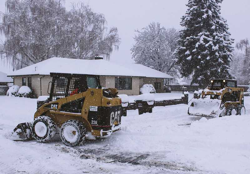 JASON CHANEY - A couple of good neighbors piloting plows dig people out of their driveways early Monday morning.