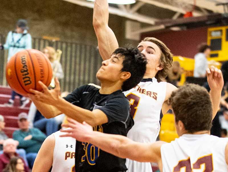 LON AUSTIN/CENTRAL OREGONIAN - Jesse Sanchez goes to the basket for two of his eight points on Thursday during the Cowboys' close loss to the Redmond Panthers.