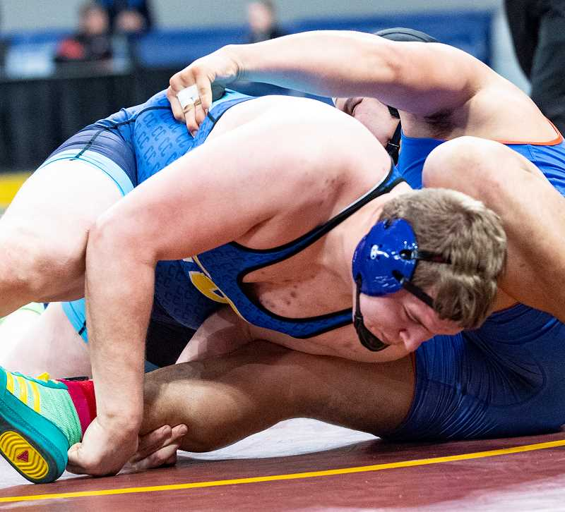 LON AUSTIN/CENTRAL OREGONIAN - Caleb Parrott works to gain control of Churchill's Jayden deFond during the 285-pound third-place match. Parrott went on to win the match by fall.