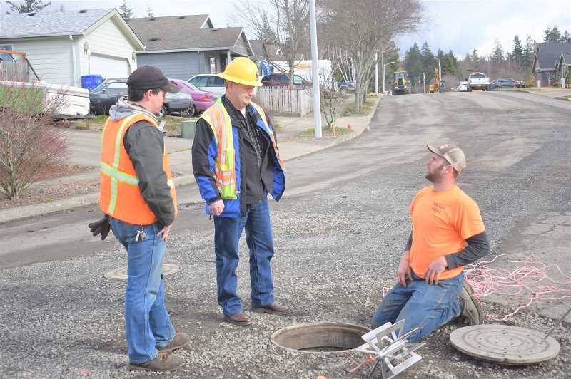 PMG PHOTO: EMILY LINDSTRAND - Estacada Public Works Director Tom Seal (center) talks with city utility workers as they work on pipes for a new subdivision.