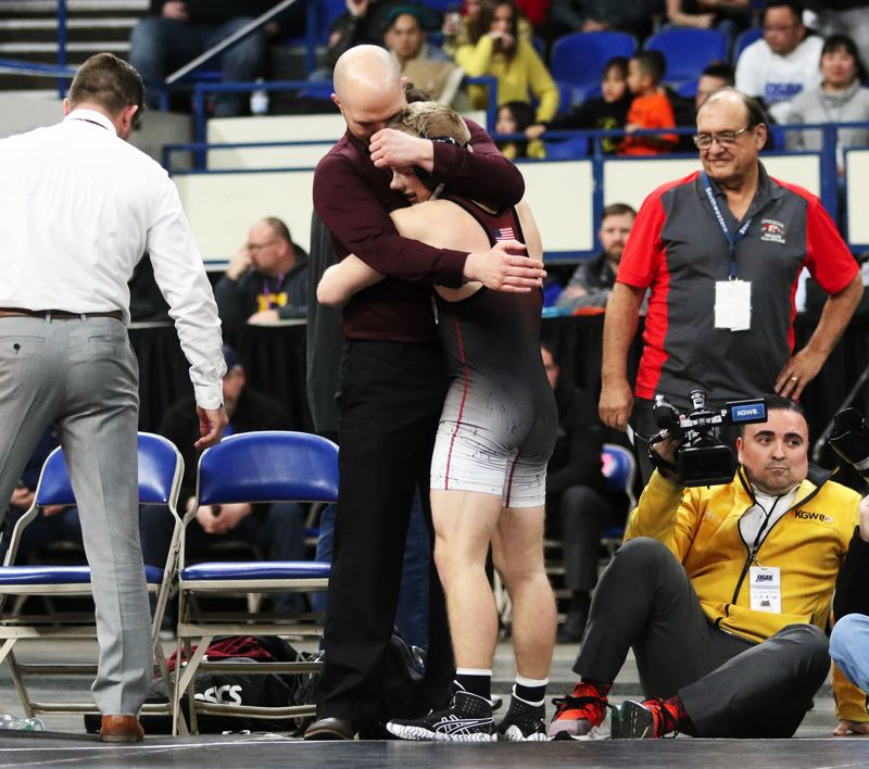 PMG PHOTO: DAN BROOD - Sherwood High School senior Gaven Jolley gets a hug from Bowmen coach Jeff Wilson after winning a Class 6A state wrestling title on Saturday.