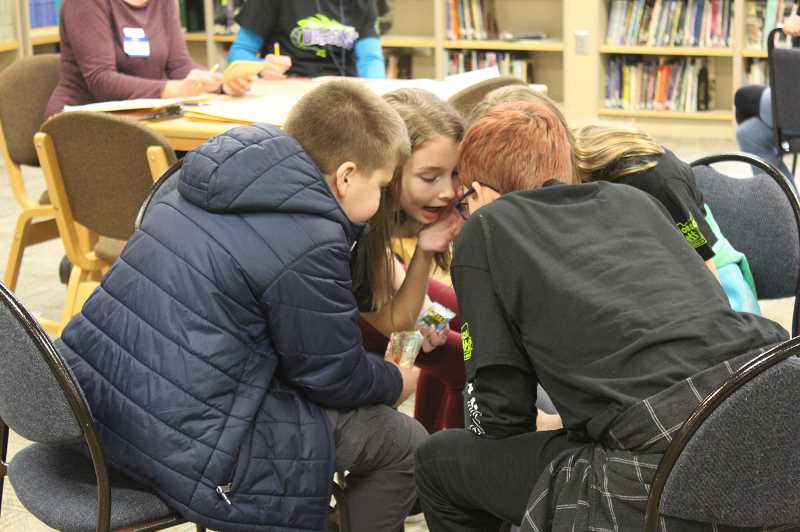 KRISTEN WOHLERS - Team members from Knight Elementary confer with one another during the 6th-8th grade district OBOB tournament.
