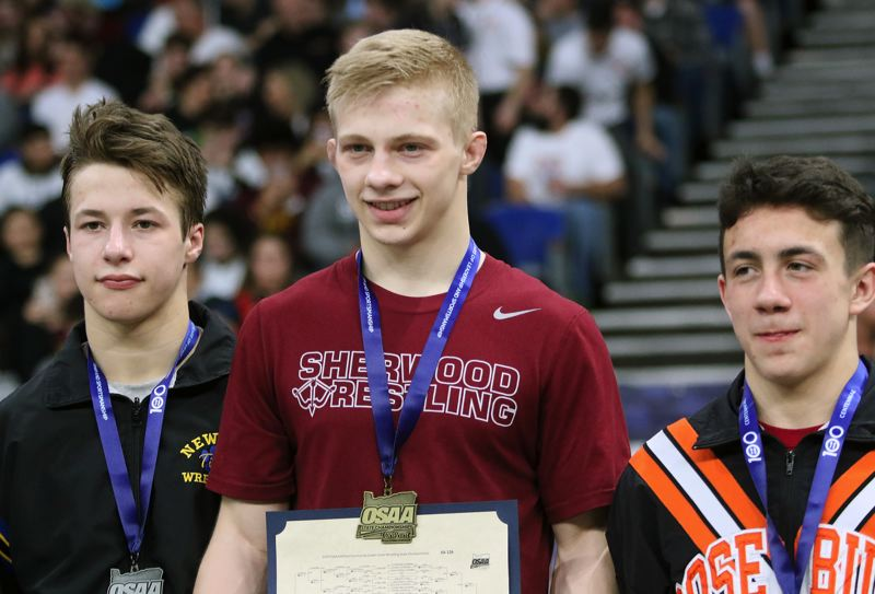 PMG PHOTO: DAN BROOD - Sherwood High School senior Gaven Jolley (center) gets his state championship medal following his victory in the 126-pound title bout at the Class 6A state tournament.