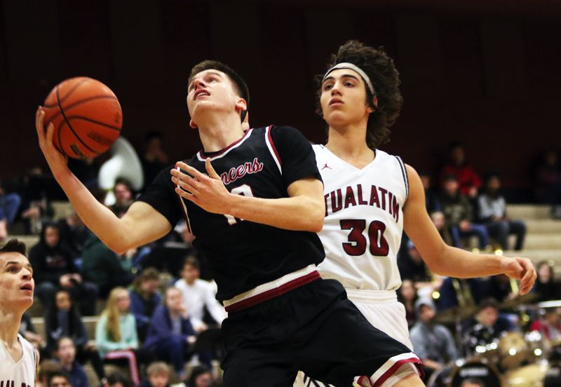 PMG PHOTO: DAN BROOD - Sandy High School senior Colton Gorski (left) looks to go to the basket against Tualatin senior Bridger Steppe during Tuesday's state playoff game.