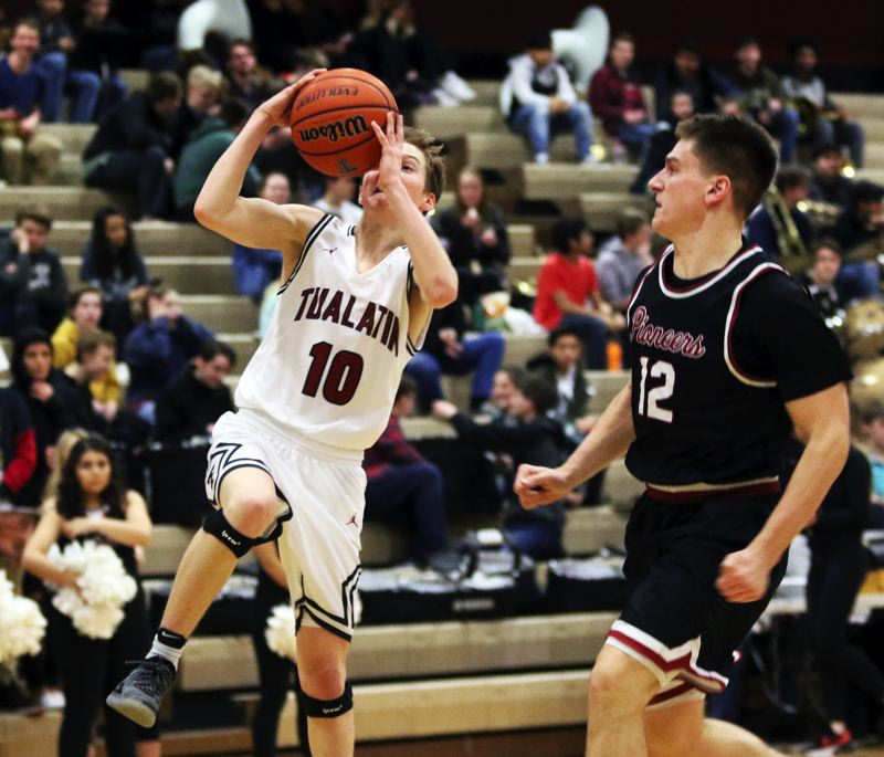 PMG PHOTO: DAN BROOD - Tualatin High School senior guard Derek Leneve (left) looks to go up to the basket on a fast break during the Wolves' state playoff game with Sandy.