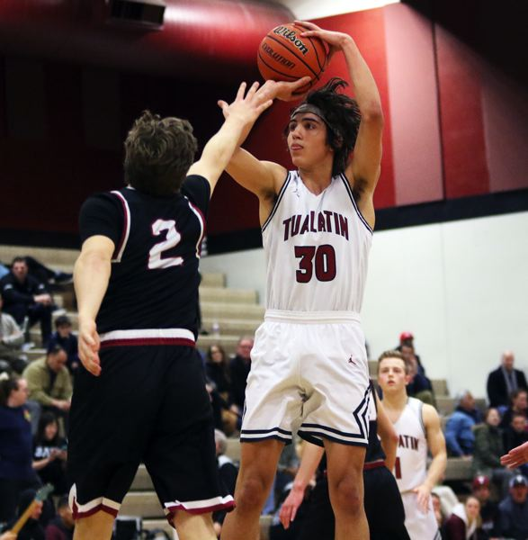 PMG PHOTO: DAN BROOD - Tualatin senior Bridger Steppe (right) takes a jump shot over Sandy junior Colby Carson during Tuesday's state playoff game.