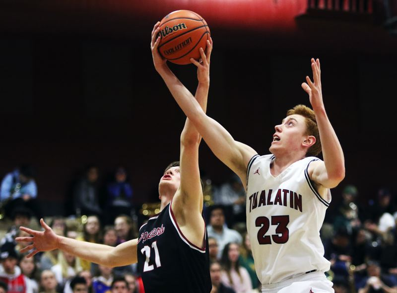 PMG PHOTO: DAN BROOD - Tualatin senior Jack Rose (right) and Sandy junior Kaleb Hubbard both reach for a rebound during Tuesday's Class 6A state playoff game.