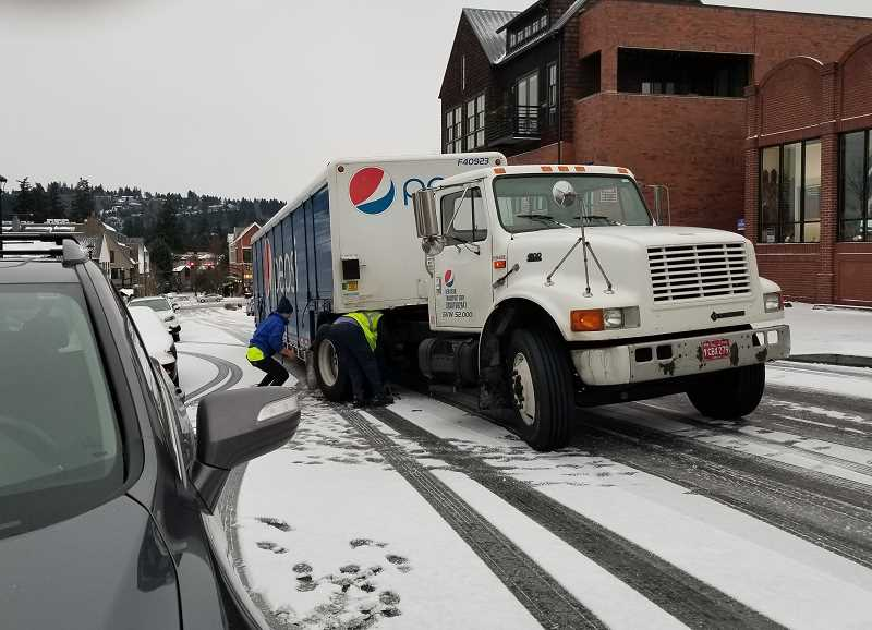 REVIEW PHOTO: GARY M. STEIN - A Pepsi delivery crew chains up Wednesday morning after their truck got stuck on an icy Second Street near B Avenue in Lake Oswego.