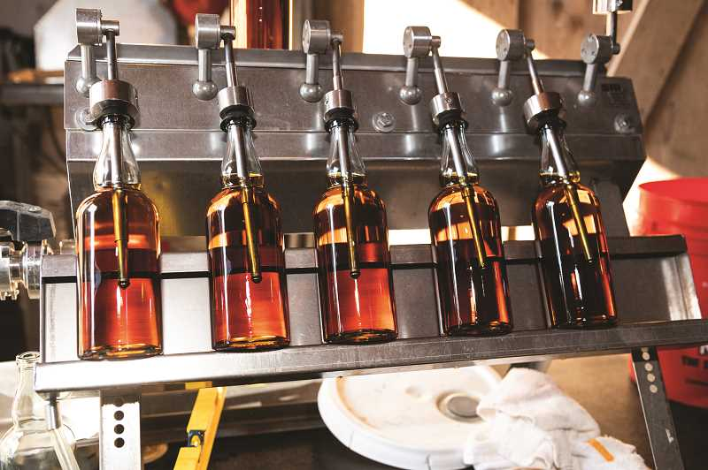 STAFF PHOTO: CHRISTOPHER OERTELL - Bottles of four-year-old whiskey are filled at the distillery at the McMenamins Cornelius Pass Roadhouse in Hillsboro, Ore., on Thursday, Jan. 31, 2019.
