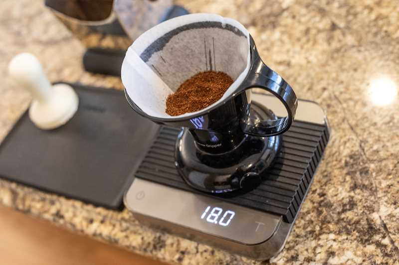 PMG PHOTO: JONATHAN HOUSE - Coffee expert Zach Perkins uses a Clever Dripper and a scale when making the perfect cup of coffee at home or while traveling.