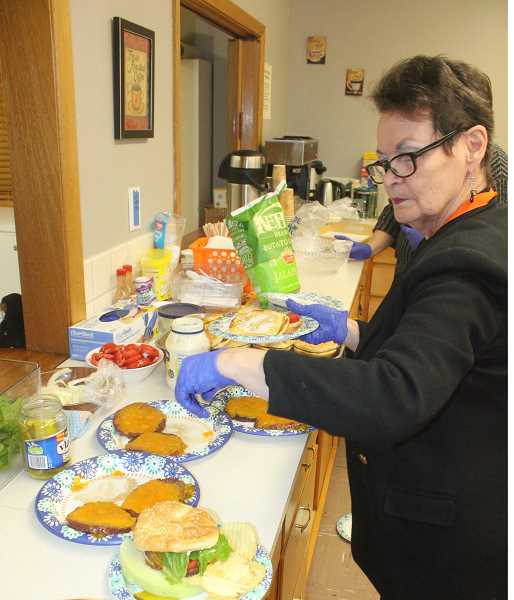 SUSAN MATHENY/MADRAS PIONEER -  Pat Abernathy, the shelter's director, sets out the plates for the overnight guests.