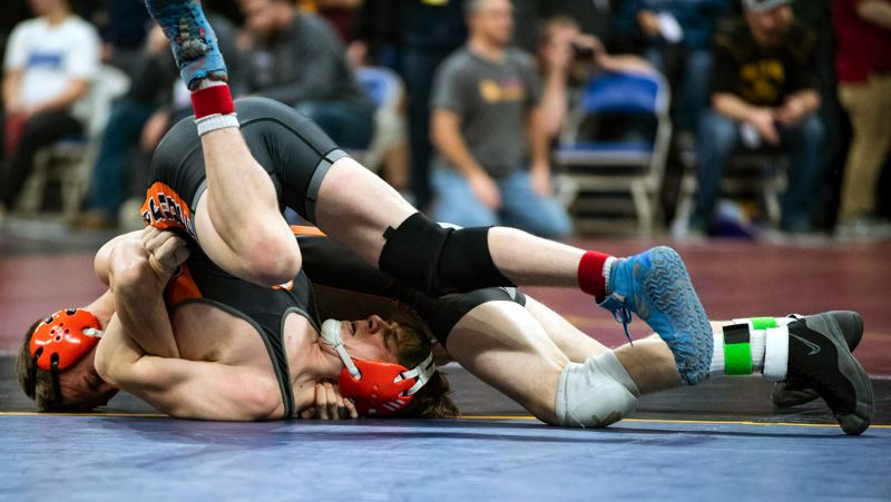 PAMPLIN MEDIA GROUP: LON AUSTIN - Ashton Kauffman (top), a state qualifier at 138 pounds, takes on an opponent in the Class 5A meet at Veterans Memorial Coliseum.