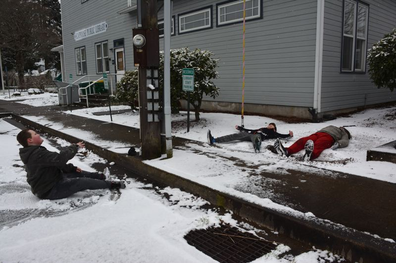 PMG PHOTO: COURTNEY VAUGHN - Scappoose residents Triston, Isaiah and CJ make snow angels and snowballs during a day when school was closed due to weather conditions Wednesday, Feb. 27. Schools throughout Columbia County announced closures Wednesday, and many evening governmental meetings were canceled.