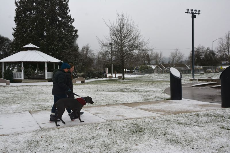 PMG PHOTO: COURTNEY VAUGHN - Bonnie and Brooklyn Johnson of Scappoose walk their dog, Mena, through the snow in Heritage Park in Scappoose after a Wednesday morning snowfall.