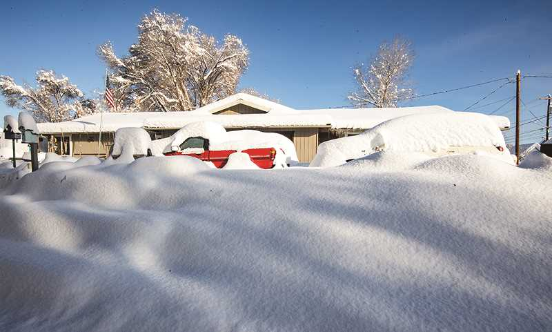 LON AUSTIN - Homes and vehicles are still buried under nearly 2 feet of snow.