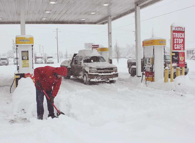 TONY AHERN/MADRAS PIONEER - Ryan Morrison clears snow around the bays at the Madras Truck Stop Monday morning. Heavy snow fell late Sunday-early Monday throughout Central Oregon, closing schools and other businesses. The late-season snowstorm was expected to continue through Friday morning.