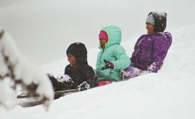 HOLLY M. GILL/MADRAS PIONEER - From left to right, Benitez children, Eli, 6, Isabella, 7, and Alessandra, 11, of Madras, enjoy a fast sled ride down a steep hill south of town on Monday. In some areas around Madras, about two feet of snow had accumulated by Tuesday morning.