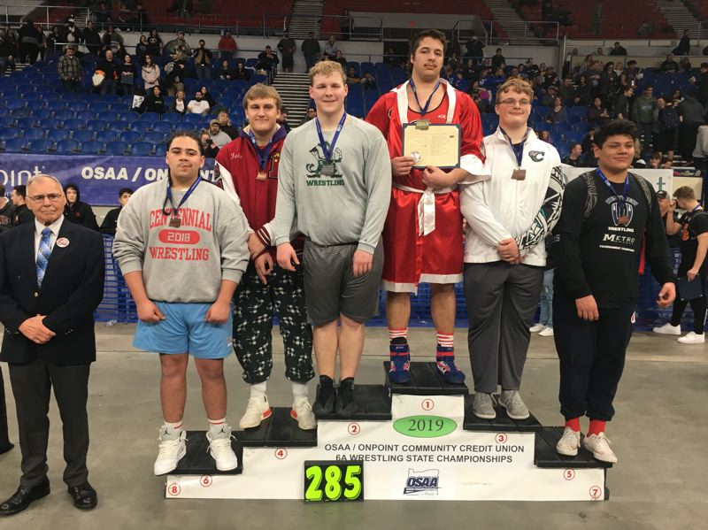 PMG PHOTO: JIM BESEDA - Oregon City's Lane Marshall stands atop the podium after going 4-0 with four pins to clinch the 285-pound title at the OSAA Class 6A wrestling state championships at Memorial Coliseum.