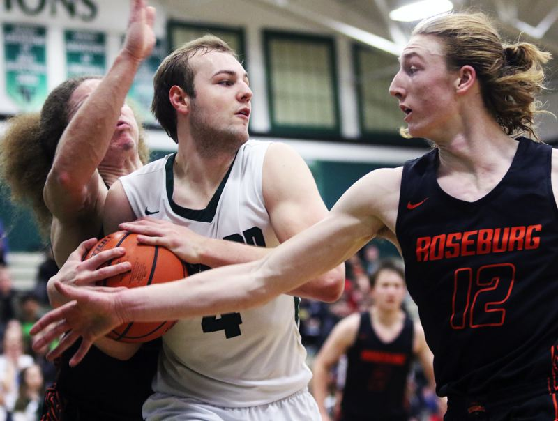 PMG PHOTO: DAN BROOD - Tigard senior Stevie Schlabach battles to keep the ball away from Roseburg seniors Collin Warmouth (12) and D'Angelo Adams during Tuesday's state playoff game.