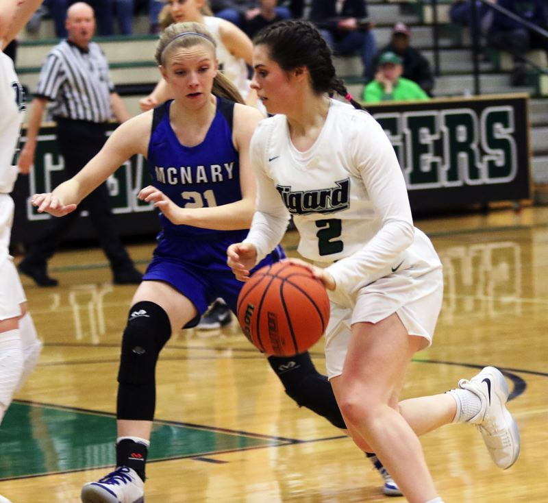 PMG PHOTO: DAN BROOD - Tigard junior Kennedy Brown (right) drives against McNary's Abigail Hawley during Thursday's Class 6A state playoff game.