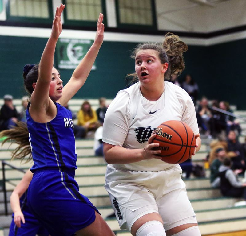 PMG PHOTO: DAN BROOD - Tigard High School senior post Dani Lyons (right) looks to go up to the basket during the Tigers' win over McNary in Thursday's Class 6A state playoff game.