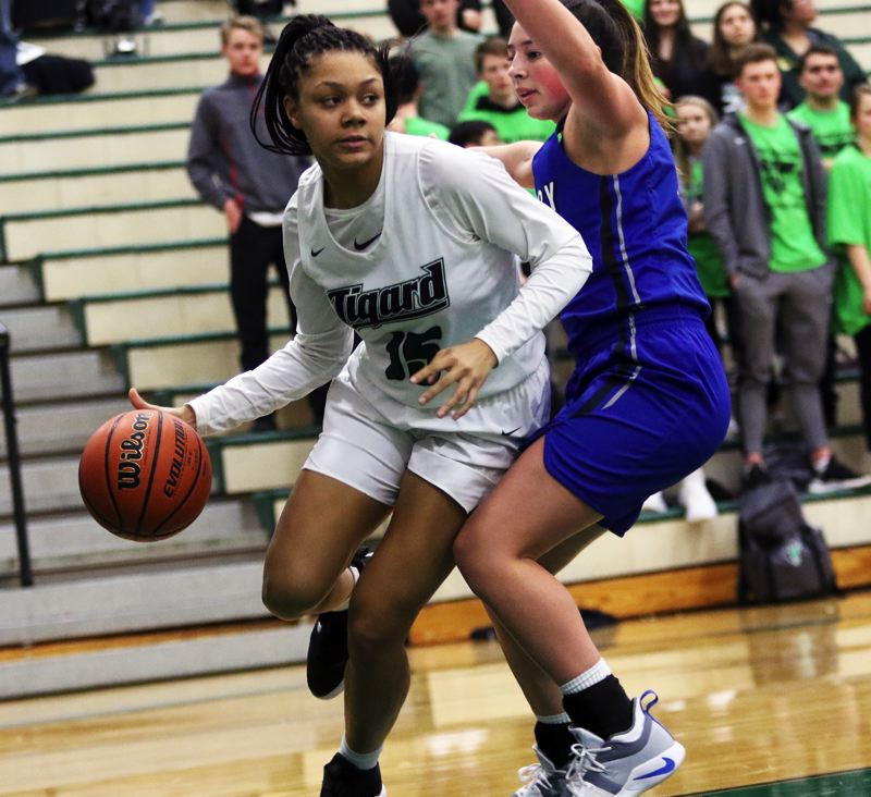 PMG PHOTO: DAN BROOD - Tigard High School sophomore Ajae Holdman (left) drives the baseline during the Tigers' state playoff win over McNary.