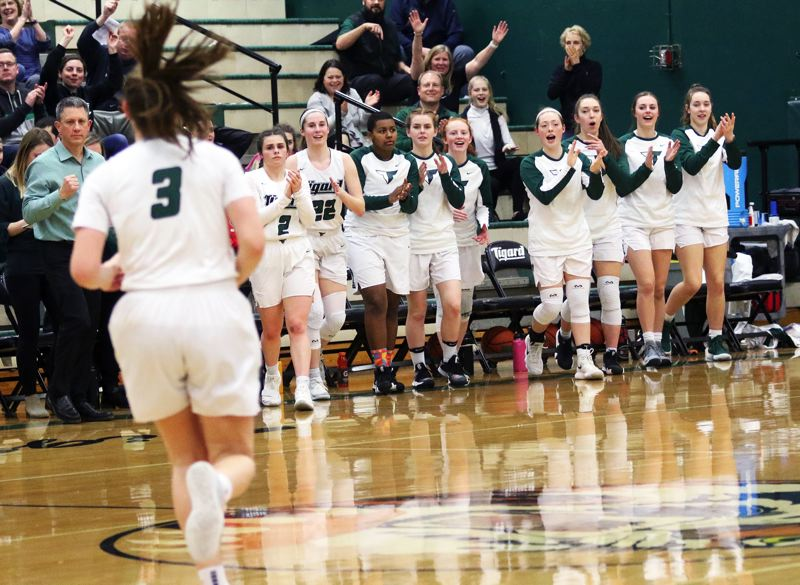 PMG PHOTO: DAN BROOD - Tigard players wait to greet senior Campbell Gray (3) following her buzzer-beating put-back basket at the end of the first quarter of Thursday's state playoff game.