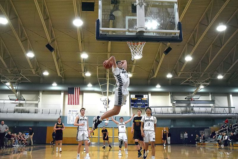 PMG PHOTO: TANNER RUSS - Wilsonville's Dakota Reber takes flight for a dunk during his team's 79-31 home win over Crescent Valley in the first round of the Class 5A state playoffs on Friday.