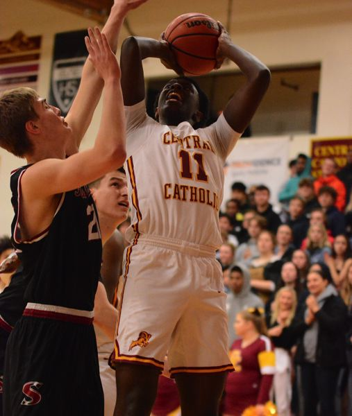 PMG PHOTO: DAVID BALL - Central Catholics Darius Gakwasi goes up for a close-range two against Sandys Kaleb Hubbard during the Rams 66-43 second-round playoff win Friday.